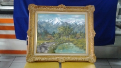 A fine oil on canvas painting depicting snow covered mountains and a village signed circa 1960
