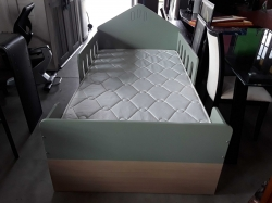 Children's bed with mattress and wall shelf