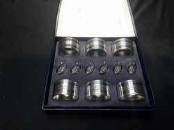 A boxed vintage set of 6 silver plate napkin rings & 6 cast swans for table places